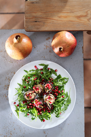 Healthy eating. Eggplant roulades with cheese served with pomegranate on rocket lettuce.
