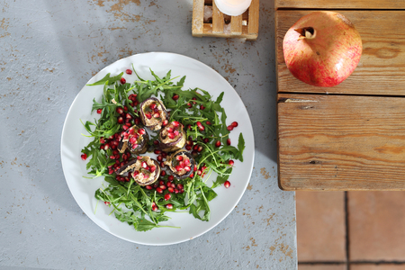 Veg salad with eggplant. Eggplant roulades with cheese served with pomegranate on rocket lettuce.