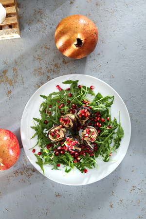 Dietary dish with eggplant. Eggplant roulades with cheese served with pomegranate on rocket lettuce. Reklamní fotografie