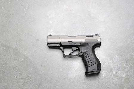 Pistol. Gun on a gray background.