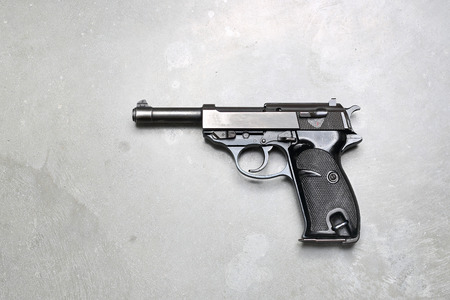 Short weapon. Gun on a gray background. Stock Photo