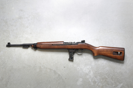 Weapon. Windbreaker, rifle on a gray background. Stock Photo