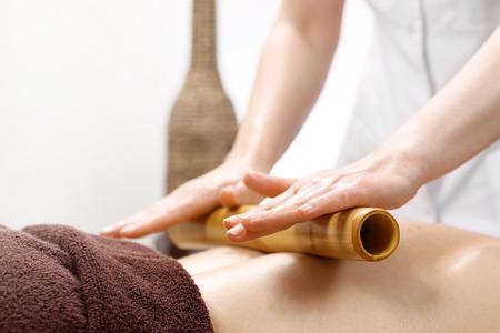 Bamboe massage. De masseur masseert het lichaam met bamboestokken. Stockfoto - 109075731