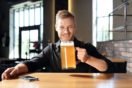 Beer mug. Smiling handsome man with a glass of wheat beer.
