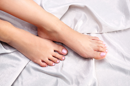 Bare female feet. Feminine feet in satin bedding in powder pink color.