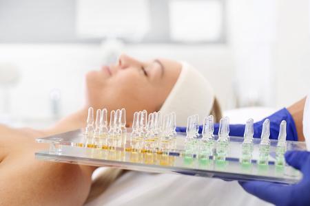 Kosmetik in einer Ampulle. Die Kosmetikerin hält ihre Hände mit kosmetischen Präparaten in der Hand. Standard-Bild