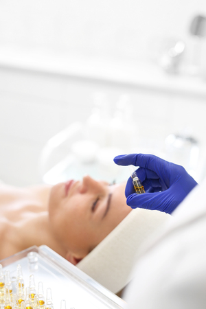 Chemical peeling, exfoliating treatment. Beautician imposes on the woman's face a cosmetic preparation. Imagens