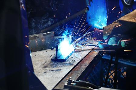 Welder. The man is welding in the workshop. Imagens