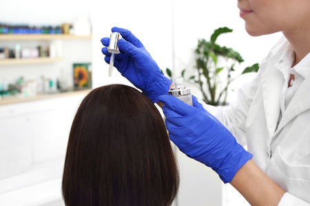 Anti-dandruff treatment. Hair care. The dermatologist looks for the preparation of the womans scalp. Banco de Imagens
