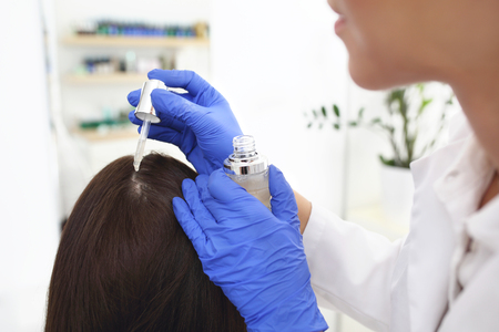Dandruff. The dermatologist applies the remedy to the womans scalp. 스톡 콘텐츠