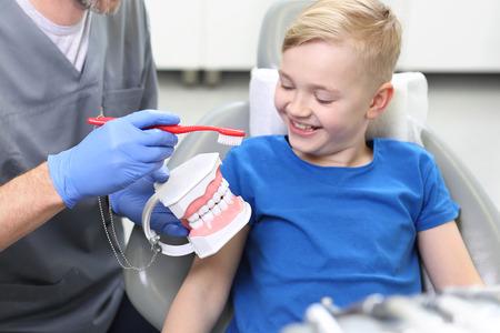 Cepillado de dientes adecuado, niño en el dentista