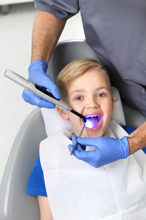 Child at the dentist. Light-curing seal, a child in a dental office Stockfoto
