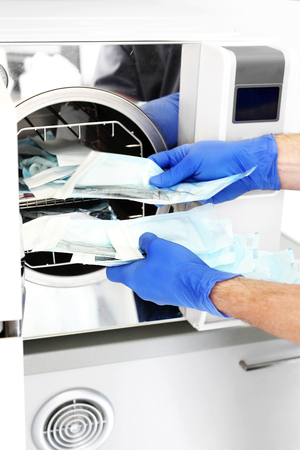Sterilization of medical instruments. The doctor removes sterile packages prepared for the procedure.