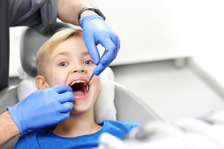 Child at the dentist. Tooth treatment, the dentist cleans the cavity