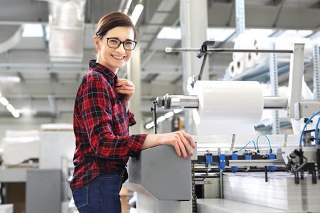 Printing house. A woman is working at a peeling machine. 版權商用圖片