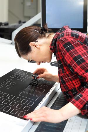 The printer checks the printout. Offset printing. Operation of the printing machine. The printer supports the control panel of the printing machine.