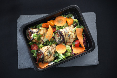 Grilled aubergine rolls with dried tomatoes and cheese served on lettuce and carrots packed in a container for food.