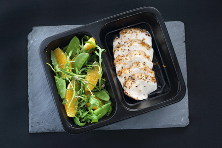 Dinner meal in a box diet. Chicken in herbs with green salad Stock Photo