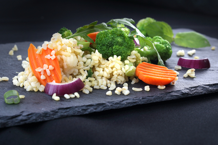 Brown rice with vegetables served on a black plate.