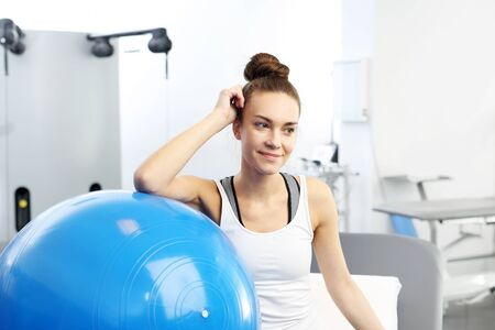Fitness trainer with a blue gym ball after training.