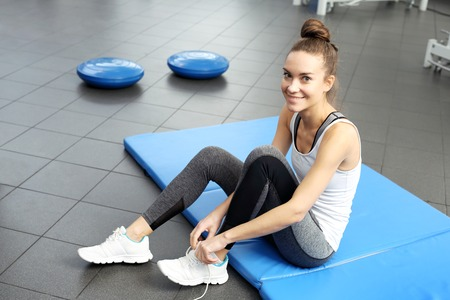 A young, attractive woman in an exercise room on a blue sports mattress.