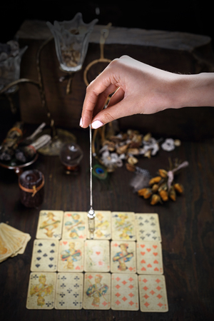 Fortune-telling, the fortune-teller puts tarot cards and spells the pendulum. Stock Photo