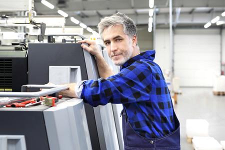 The mechanic repairs the printing machine