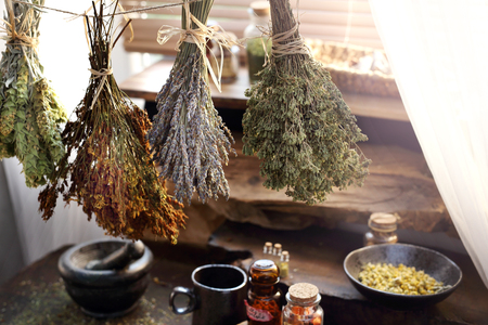 A composition of herbs, flowers and spices. Healthful potions and infusions on a wooden table. horizontal composition.