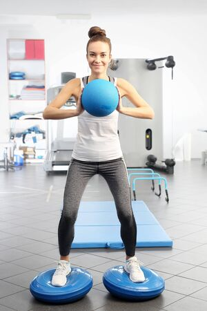 Gym training. A young woman is training on with a training ball in an exercise room. Stockfoto