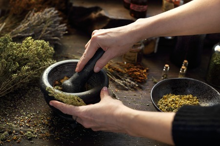 Herbalist. The woman prepares medicinal herbal mixtures. He composes herbs by grinding them in a mortar Reklamní fotografie