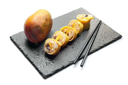 Fruit sushi, a sushi roll with mango and chocolate sauce.