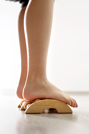 Feet of baby against the background of the wooden floor, exercises against flat feet.