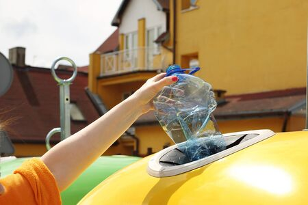 Recycling, a woman throws plastic waste into a yellow container