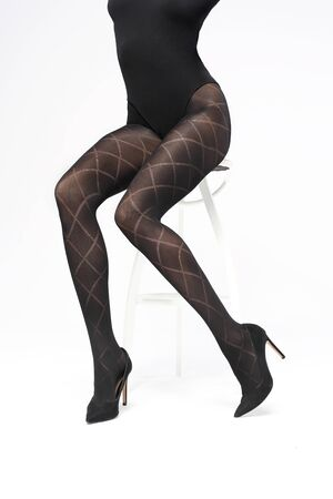 Woman's legs in black tights on a white background. Stockfoto