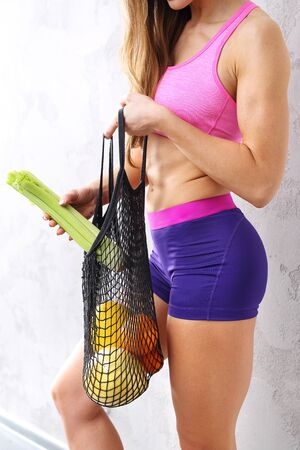 Healthy diet. An athletic woman with a bag of fresh vegetables.