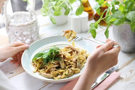 Pasta with oyster mushrooms. The woman eats a tasty dish.
