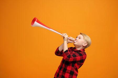 A boy with a big fan trumpet. 写真素材