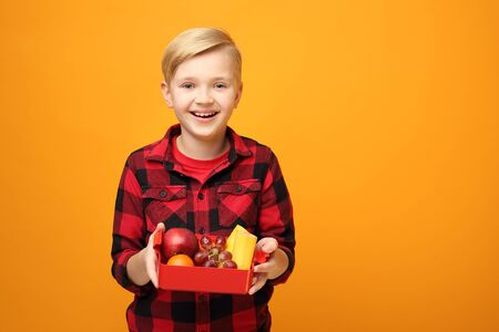 School breakfast, healthy fruit diet of the child. The boy with a wide smile expresses emotions.