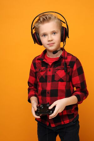 Console game. Young boy playing computer games on headphones. 写真素材