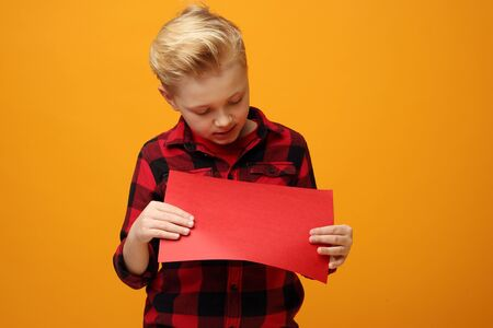Child boy holding a red sign with space for text. Beautiful smiling caucasian boy in the red shirt on the yellow