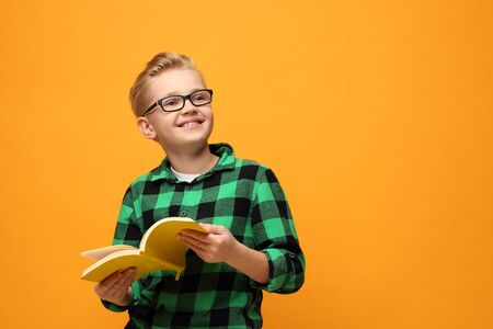 Book reading. Smiling, happy boy reading a book.