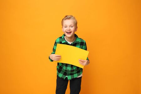 Smiling, happy boy holding a yellow sign with space for text. 写真素材