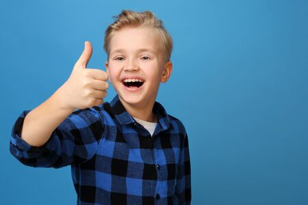 OK cheerful boy shows thumbs hand. Happy, smiling boy on a blue background expresses emotions through gestures. Archivio Fotografico