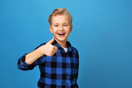 Gesture ok, cheerful boy shows thumbs hand. Happy, smiling boy on a blue background expresses emotions through gestures. Archivio Fotografico