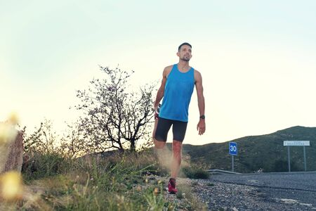 Outdoor training. A man in sports outfit runs along the mountain trail.