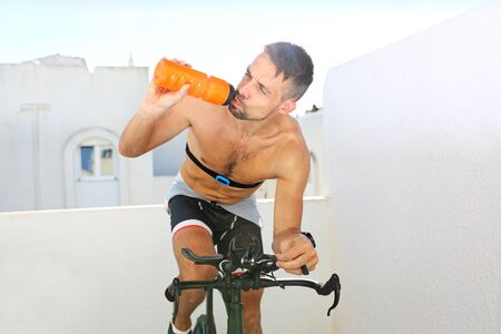 Cycling training. Hydration during training. the athlete drinks an isotonic drink while riding a bicycle.