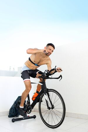 Conditioner during training. The athlete eats an energy bar riding a stationary bike. Professional athlete's diet during training.