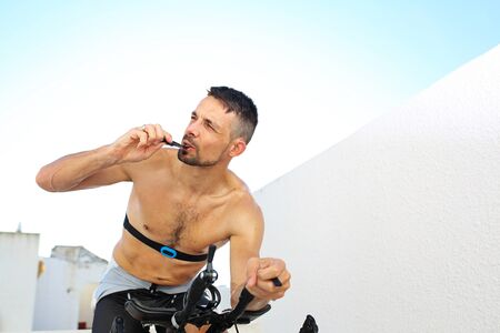 The athlete eats an energy bar riding a stationary bike.