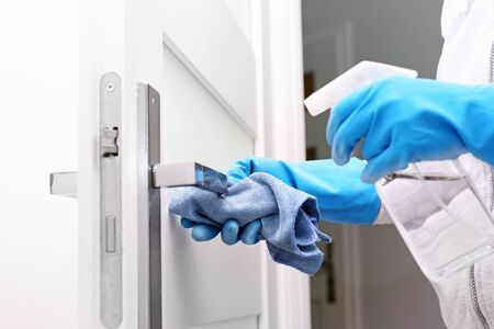 The woman cleans the apartment with glove