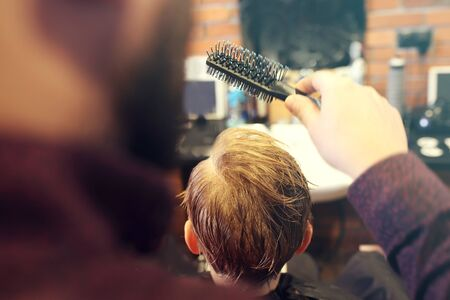 Hairdresser. A child, a boy, during a haircut at a barbershop. Archivio Fotografico